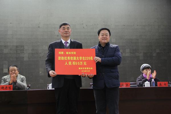 榆林市慈善协会会长刘洪(右)向榆林学院递交捐赠牌.jpg